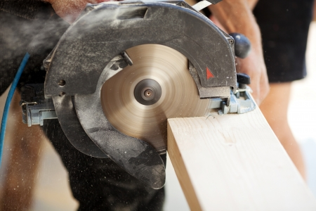 Close-up of a carpenter using a circular saw to cut a large board of wood photo