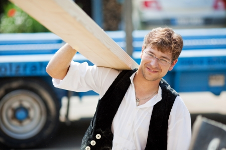carries: Smiling carpenter carrying a large wood plank on his shoulder