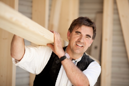 Smiling mature carpenter carrying a large wood plank on his shoulder photo