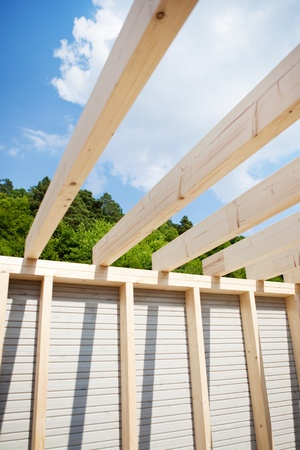 housebuilding: Roof beams of an unfinished roof with trees and sky in the background Stock Photo