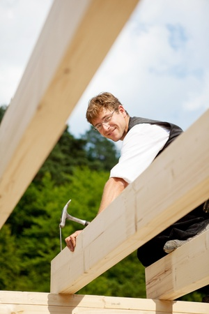 Carpenter working on the top of the roof structure and hammering a large nail photo
