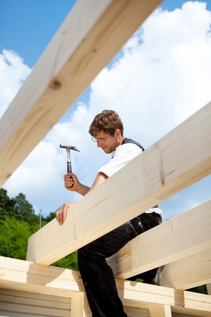 Carpenter sitting on the the roof beams and hammering a large nail photo