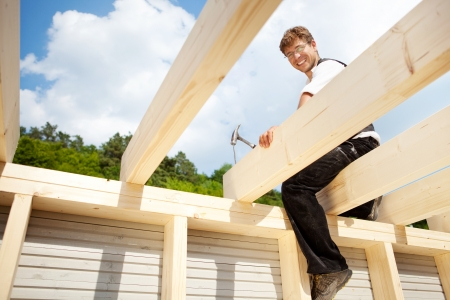 Happy carpenter sitting on the the roof beams and hammering a large nail photo
