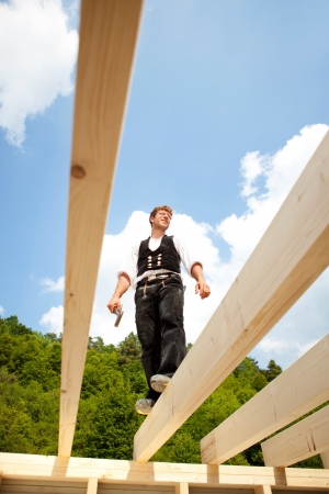 wooden beams: Carpenter standing over the unfinished roof beams while holding a hammer with trees and sky in the background