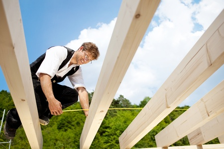 Happy carpenter measures beams with folding ruler in a bright sunny day photo
