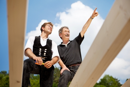 Close-up of two carpenters discussing the work on top of an unfinished roof photo