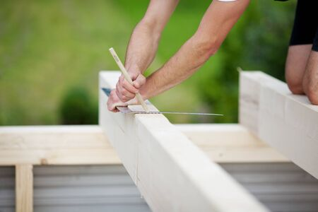 timber frame: Close-up of a carpenter making markings on a beam using a pencil and a steel square