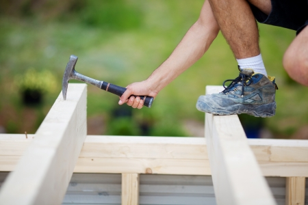 stuck up: Carpenter picking up the hammer that was stuck on the roof beam Stock Photo