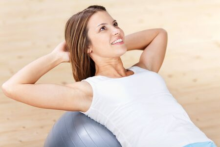 hand movements: Healthy beautiful woman exercising with fitness ball at home