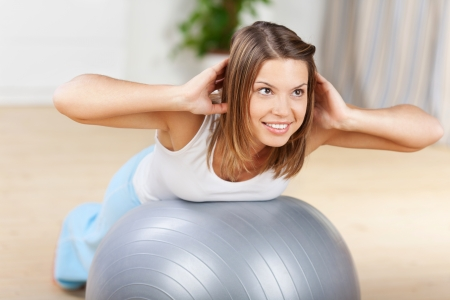 shaping: Cheerful healthy female exercising with fitness ball at home Stock Photo