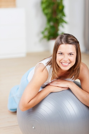 fit ball: Cheerful young female exercising with fitness ball at home Stock Photo