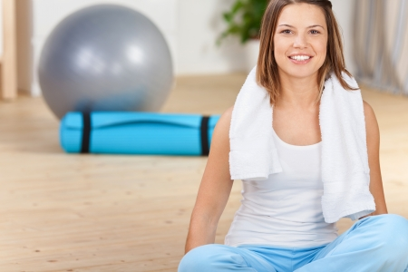 Sitting woman with towel after work out at home photo