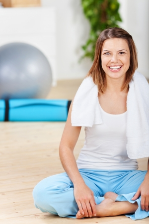 Smiling woman sitting on the floor after workout photo