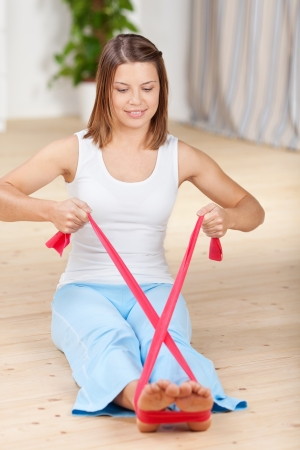 Young woman doing aerobic exercise with Theraband photo