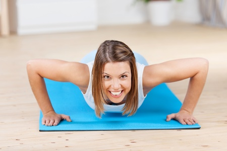 Image of a young woman exercising and laughing, looking at the camera. photo