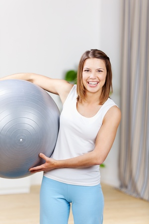Happy fit woman exercising with fitness ball photo