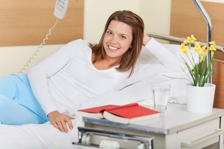 Image of a young female in the hospital, lying on bed and smiling. Stock Photo - 21110398