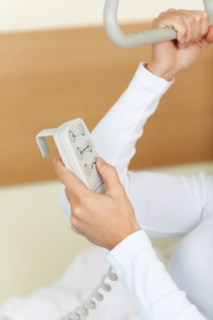 Close-up photograph of a patient adjusting the bed with a remote controller.