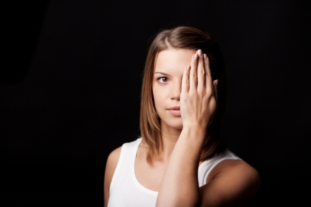 hides: Photograph of a young female model hiding her left eye by placing her hand in front of it.