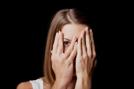 expression: Anxiety - a conceptual image of a woman covering her face with her hands and peering out with one eye between her fingers on a dark studio background