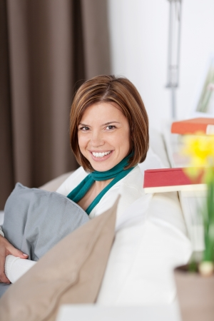 Image of a beautiful young woman relaxing on the sofa and smiling for the camera. Stock Photo - 21110419
