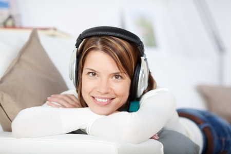 Happy woman listening to her music wearing a set of earphones and lying on her stomach on a sofa looking at the camera Stock Photo - 21110439