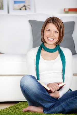 woman couch: Happy young woman sitting on the floor in her living room leaning against the sofa and holding a book on her lap Stock Photo