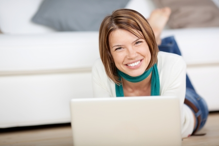 computer model: Image of a cheerful female looking at the camera while working on the laptop in the living room.