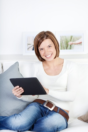 Image of a gorgeous young woman using tablet, smiling at the camera while sitting on the sofa in her living room Stock Photo - 21110542