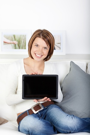 Woman displaying her tablet computer with the blank black screen turned to face the camera for your text or advertisement Stock Photo - 21110544