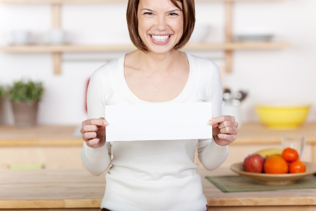 Image of an excited woman showing a sign in the kitchen. photo