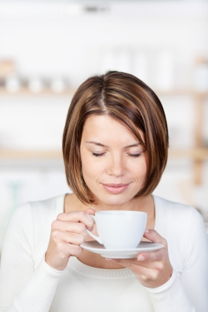one eye closed: Image of a woman drinking coffee with closed eyes, standing in the kitchen.