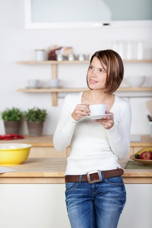 Photo of a woman standing relaxed and drinking coffee in the kitchen. photo