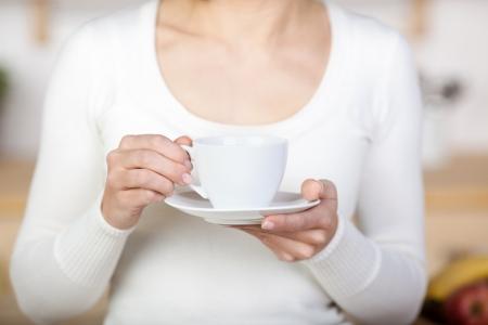 holding close: Close-up image of a woman holding a coffee mug.
