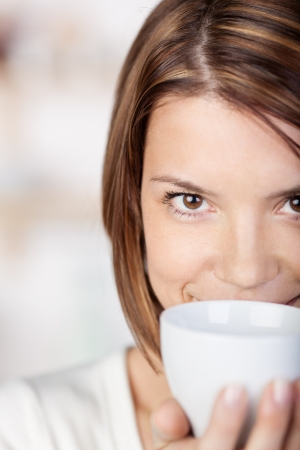Close-up portrait of a woman holding a coffee mug close to her face. photo