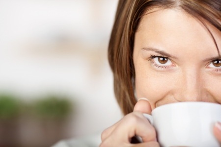 Close-up portrait of a pretty woman smiling and drinking coffee. Stock Photo - 21110571