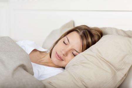 Vue de gros plan d'une belle jeune femme endormie dans son lit avec une expression pacifique Banque d'images - 21110646