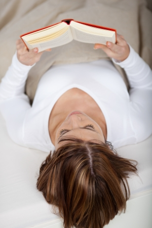 Photo of a young female lying in bed and reads a book. photo