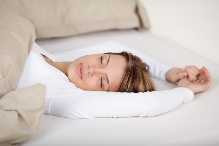 Serene woman relaxing in bed lying with her eyes closed and arms stretched above her head photo