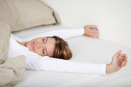 Smiling woman stretching in bed with a beautiful smile on her face as she spends a lazy day relaxing Stock Photo - 21110718