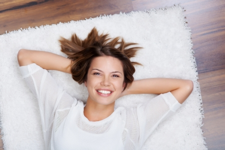 woman relaxing: Portrait of smiling woman relaxing and lying on the floor