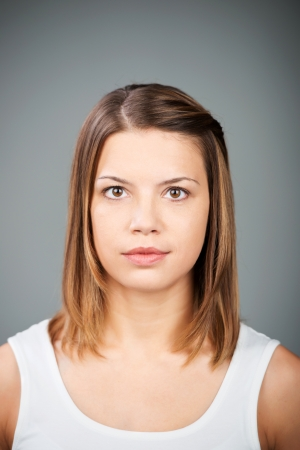 seriously: Portrait of brunette woman on a grey wall background Stock Photo
