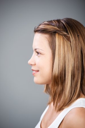 near side: Side view shot of smiling woman's face over the grey background