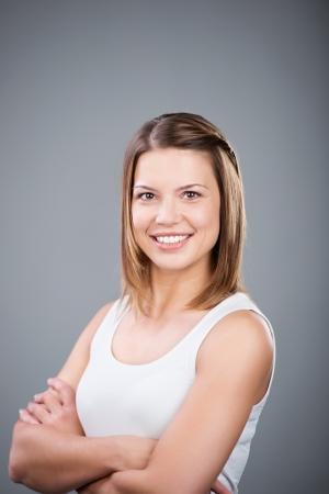 Glückliche Frau posiert mit verschränkten Armen über dem grauen Hintergrund Standard-Bild