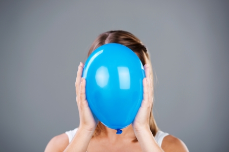 Close up of woman covering her face using blue balloon photo