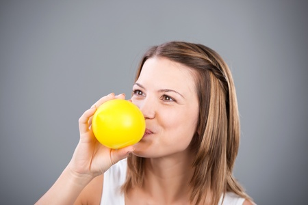 inflating: Cheerful woman blowing yellow balloon in a close up shot