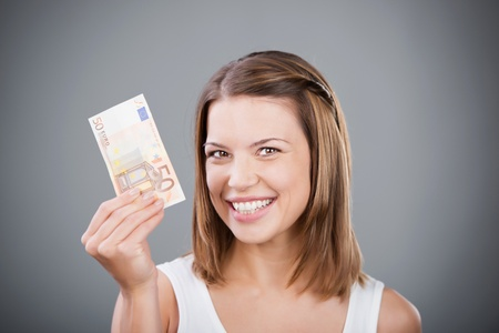 woman holding money: Happy woman holding fifty Euros over the grey background