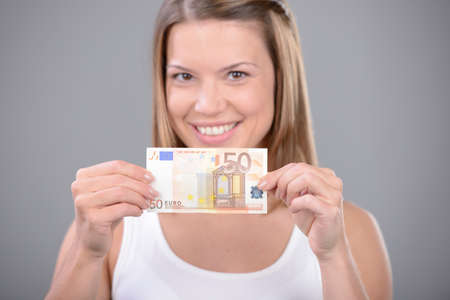 50 euro: Smiling woman shows the Fifty Euro in a close up shot