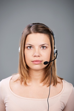 Female call center agent wearing headset over the grey background photo