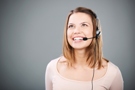 telephonic: Looking up beautiful female with headset on grey background